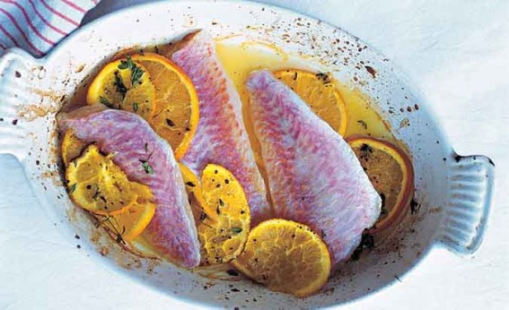 Greek red mullet with oranges and olives and sprinkling of parsley on a white dish