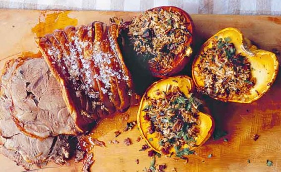 slow roast shoulder of pork with stuffed squash on a chopping board with a brown and white checked table cloth