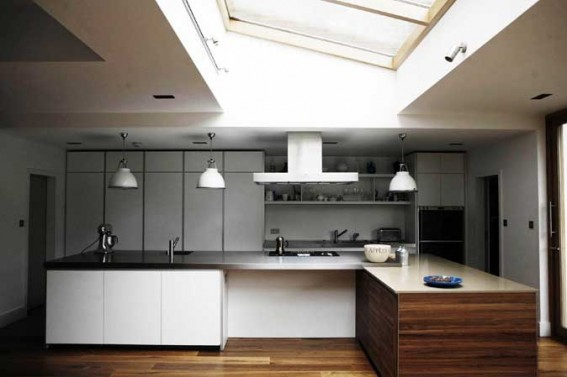 Diana Henry's kitchen with breakfast bar and cooker hood and three white pendant lights.