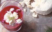 Beetroot soup with goats cheese on a wooden board with dill.