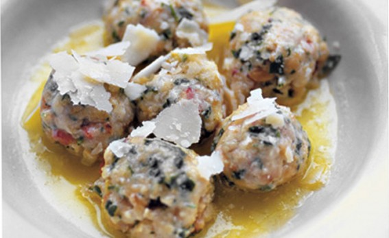 bread dumplings with pancettis and parmesan cheese on a white plate