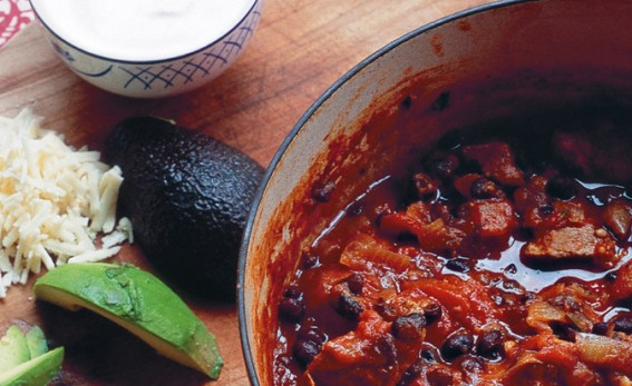 Lamb beer black bean chilli with avocados rice and cream on a brown chopping board