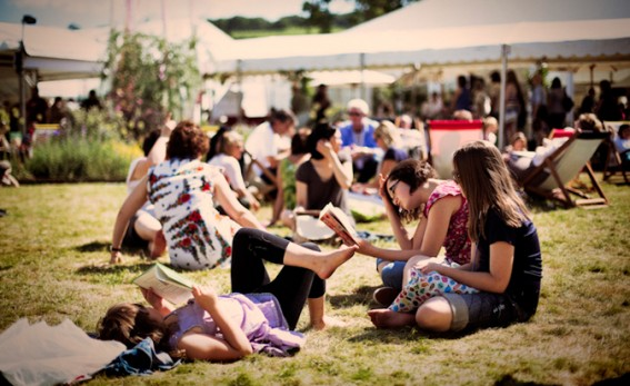 Hay Festival people sitting round in the sun reading.