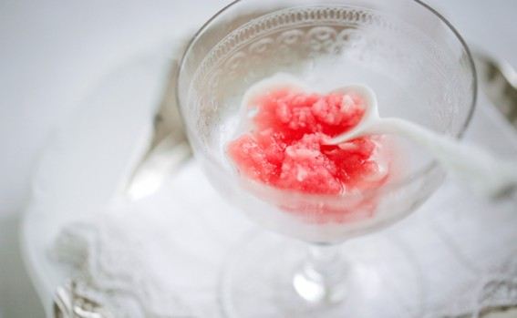 blood orange sorbet in a crystal bowl on a white table cloth with a white ceramic teaspoon.