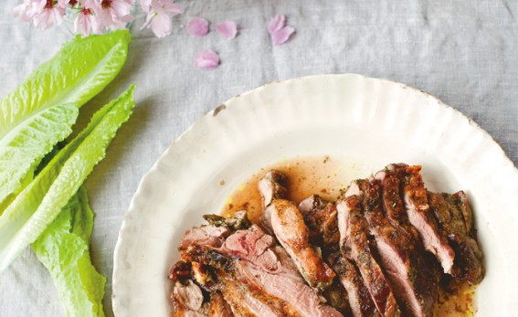 Butterflied leg of lamb with sekenjabin with lettuce leaves and pink spring petals on a white table cloth.
